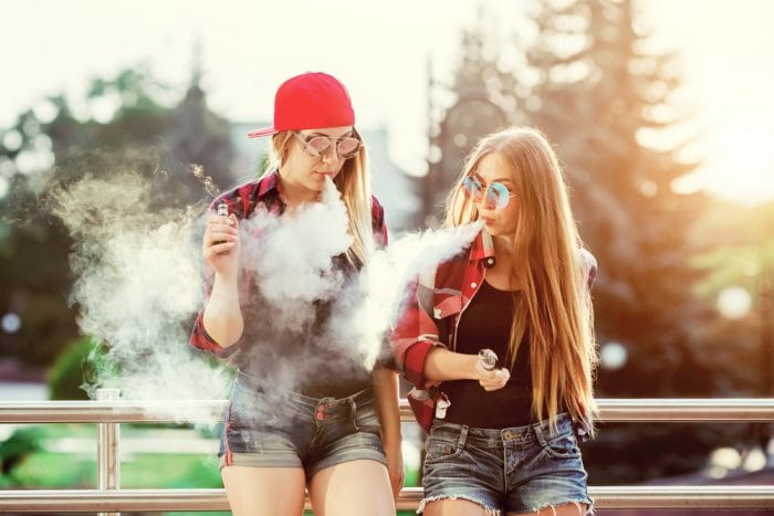 Two women vaping outdoor. The evening sunset over the city. Toned image.