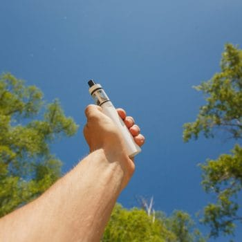 Close up of a man hand holding an electronic cigarette on sky background. Vape in summer, eco-friendly