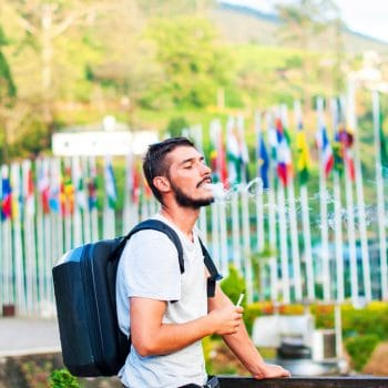 A handsome guy with a beard smokes an electronic cigarette on the background of mountains and flags of different countries