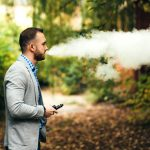 Man with beard vaping electronic cigarette outdoor