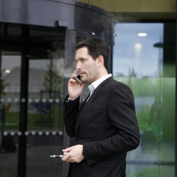 Young attractive businessman standing at office building and looking on watch