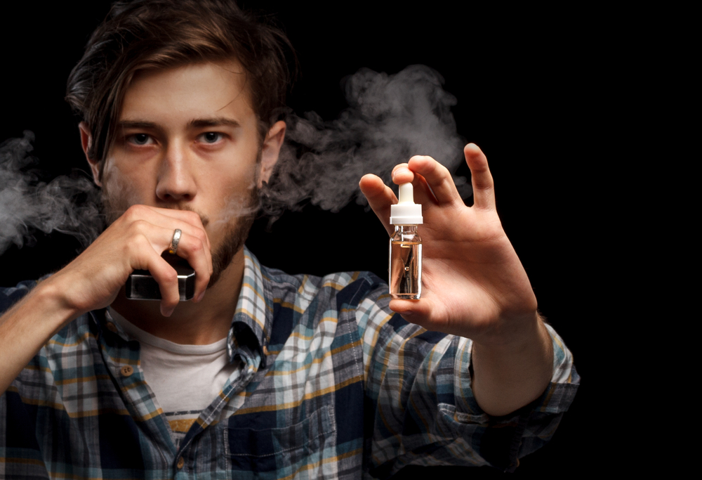 Man is vaping and holding e-liquid. Black background.