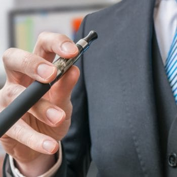 Businessman holds e-xigarette or vaporizer in hand.