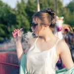 blonde young lady in a spring outfit, smoking a pink colored vape kit