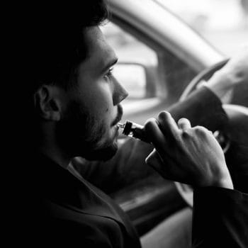 View from the side of a young man smoking an e-cigarette as he drives his car on an urban street