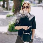 young beautiful girl enjoys electronic cigarette the Sunny weather