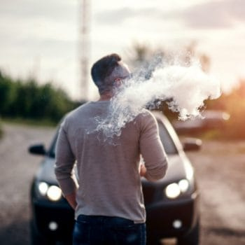 Men with beard vaping outdoor in sunglasses, focus on steam