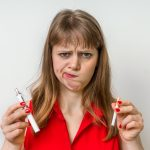 Young woman have a choice between tobacco cigarette and electronic cigarette
