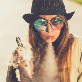Pretty young hipster woman in black hat vape ecig, vaping device at the sunset. Toned image