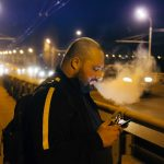 Vaping by electronic cigarette fat man using smart-phone on the bridge at night city.