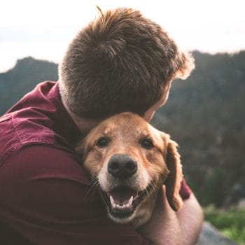 Man in red shirt hugging dog